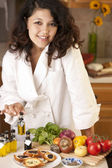 Real. Mixed race young adult woman making bruschetta — Stock Photo