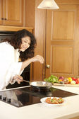 Real. Mixed race young adult woman making a meal — Stock Photo