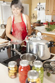 Canning. Mixed race young adult woman canning homegrown fruits and vegetables — Stock Photo