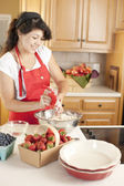 Baking. Mixed race young adult woman baking fruit pies for dessert in the kitchen — Stock Photo