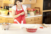 Baking. Mixed race young adult woman peeling apples to bake a fresh pie — Stock Photo