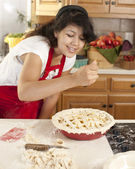 Baking. Mixed race young adult woman adds spices as she makes a fresh apple pie — Stock Photo