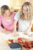 Baking. Caucasian mother and daughter in the kitchen kneading dough to make a fruit dessert — Stock Photo