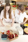 Baking. Caucasian mother and daughter in the kitchen rolling dough to make a fruit dessert — Stock Photo