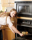 Baking. Caucasian teenage girl putting a fruit pastry in the oven. — Stock Photo