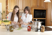 Canning. Caucasian mother and teenage daughter canning homegrown fruits and vegetables — Stock Photo