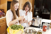 Canning. Caucasian mother and teenage daughter canning homegrown vegetables — Stock Photo