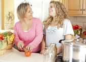 Canning. Laughing caucasian laughing mother and teenage daughter canning homegrown fruits and vegetables — Stock Photo