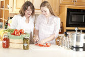 Canning. Caucasian mother helping her teenage daughter can homegrown fruits and vegetables — Stock Photo