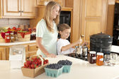 Canning. Mother and son canning homegrown fruits for preserves — Stock Photo