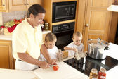 Canning. Father and his two sons canning homegrown fruits and vegetables — Stock Photo