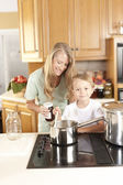 Canning. Mother and son canning homegrown fruits and vegetables — Stock Photo