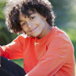 Mixed mixed race little boy sitting in the sunny park — Stock Photo