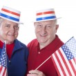 Caucasisenior adult patriotic couple waving americflags and wearing hats with stars and stripes — Stock Photo #21417101