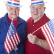 Caucasian senior adult patriotic couple waving american flags and wearing hats with stars and stripes — Stock Photo
