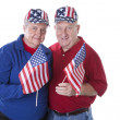 Caucasian  senior adult patriotic couple waving american flags and wearing hats with stars and stripes — Stockfoto