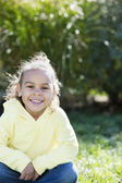 Real : Smiling mixed race little girl sitting happily in a sunny park — Stock Photo