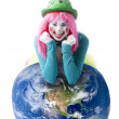 Clowns. Young teenage female clown leaning on a world ball — Stock Photo #21424047