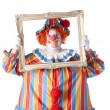 Stock Photo: Clowns. Adult male clown holding a picture frame around his face