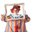 Royalty-Free Stock Photo: Clowns. Adult male clown holding a picture frame around his face