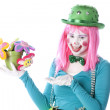 Clowns. Young teenage female clown holding a pot of flowers — Stock Photo