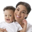 Smiling mother holding her toddler son — Stock Photo #21424753