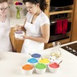 Rainbow Cake. Chefs mixing the colorful batter to prepare the layers — Stock Photo #21425485