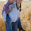 Young midwestern cowgirls play piggyback - Stockfoto