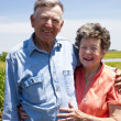 A proud hardworking midwestern grandmother and grandfather, farmers, stand proudly together in love - Stock Photo