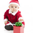 A happy little baby plays with a wrapped christmas gift package — Stock Photo