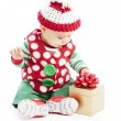 Hispanic baby boy dressed as santas plays with christmas present — Stock Photo
