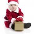 A happy little baby plays with a wrapped christmas gift — Stock Photo