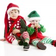 Little boy and baby sister are dressed as christmas elves - Stock Photo