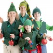 Family of christmas elves is tangled in string of holiday lights and holding christmas ornaments — Stok Fotoğraf #21427273