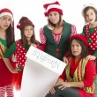 A hispanic family of christmas elves is surprised and disappointed - Stock Photo