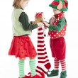 Two little Christmas elves put gifts in christmas stocking for santclaus — Photo #21427307