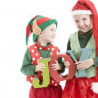 Two young christmas elves laught and hold wooden letters to spell JOY — Stock Photo
