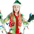 Santas christmas elf tangled in holiday lights - Stock Photo