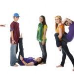 mångkulturella tonåringar arbeta tillsammans för att bilda bokstäver i alfabetet med sina kroppar — Stockfoto
