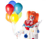 Clowns. Female clown holding a bunch of colorful helium balloons — Stock Photo