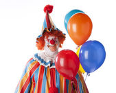 Clowns. Adult male clown holding colorful helium balloons — Stock Photo