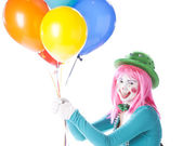 Clowns. Young teenage female clown holding a bunch of colorful helium balloons — Stock Photo