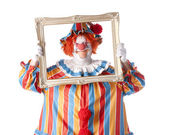Clowns. Adult male clown holding a picture frame around his face — Stock Photo