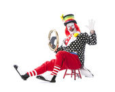 Clowns. Adult clown sitting with a steering wheel pretending to drive — Stock Photo