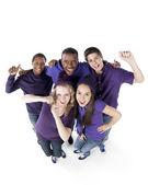 Sporseverler. grup gülümseyen genç arkadaş olarak birlikte mor takım ayakta — Stok fotoğraf