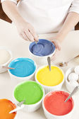 Rainbow Cake. chef mixes the colorful batter to prepare the layers for dessert — Stock Photo