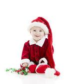 Malý chlapeček oblečený jako santa claus hraje vánoční stuhou. — Stock fotografie