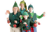 A family of christmas elves is tangled in a string of holiday lights and holding christmas ornaments — Stock Photo