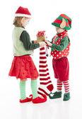 Dos pequeños duendes de navidad ponen los regalos en un calcetín de navidad de santa claus — Foto de Stock