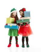 Iki küçük kız christmas elfler sarılmış hediyeler uzun boylu yığını yürütmek — Stok fotoğraf